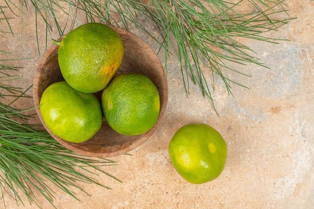 Cuenco de madera de mandarinas frescas verdes sobre la superficie de mármol.