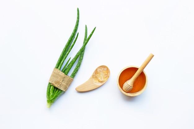 Cuenco de madera de miel y aloe vera. ingredientes naturales para el cuidado casero de la piel en blanco.