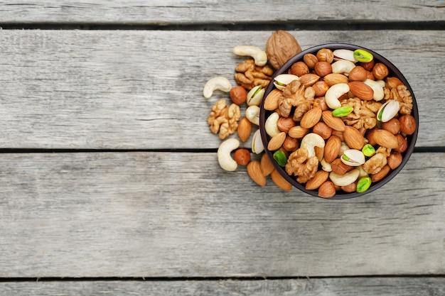 Cuenco de madera con nueces mixtas en un gris de madera. nueces, pistachos, almendras, avellanas y anacardos, nueces.