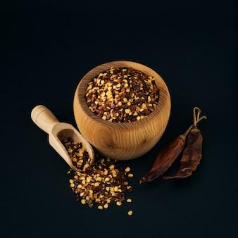 Cuenco de madera de pimienta de cayena roja triturada, hojuelas de chile seco y semillas sobre un fondo negro
