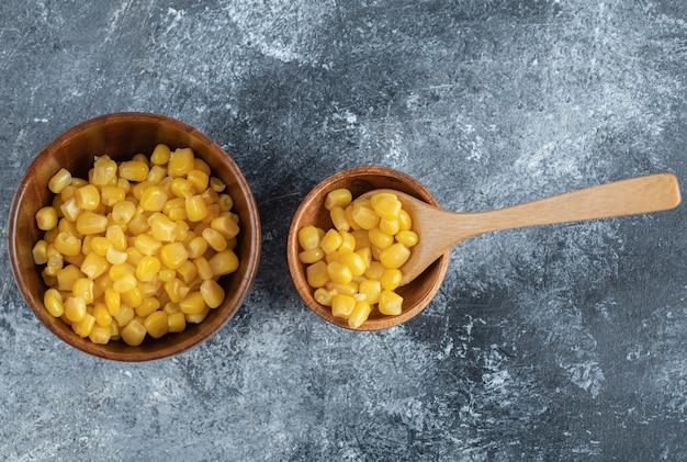 Un cuenco de madera de semillas de palomitas de maíz en mármol.
