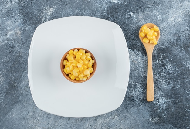 Un cuenco de madera con semillas de palomitas de maíz en un plato vacío.