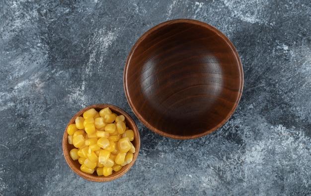 Un cuenco de madera vacío con un cuenco pequeño de semillas de palomitas de maíz.