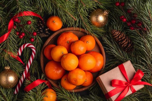Cuenco de mandarinas sobre la mesa decorada con ramas de pino de navidad, juguetes, regalos.