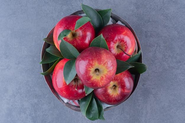 Un cuenco de manzanas con hojas sobre la mesa de mármol.