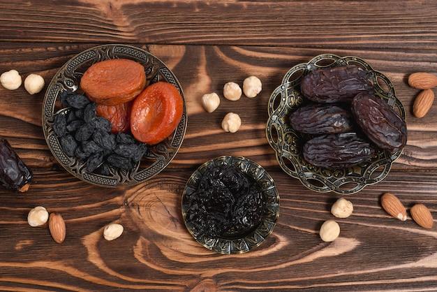 Cuenco metálico de albaricoque seco; pasa; fechas; almendras y avellanas en mesa de madera.
