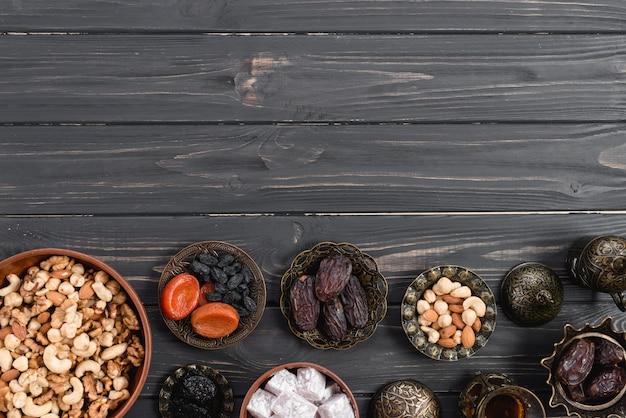 Cuenco metálico con dulce lukum; frutos secos y nueces en el escritorio de madera negro para ramadan