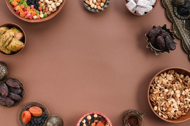 Cuenco metálico y terrestre de frutos secos; fechas; lukum; nueces y baklava dispuestos en forma circular sobre el fondo marrón