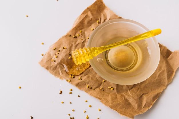 Cuenco de miel; cucharón y semillas de polen de abeja sobre papel marrón