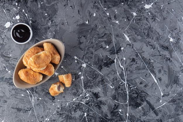 Un cuenco de mini croissants con chocolate colocado sobre un fondo de mármol.