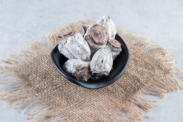 Cuenco negro de frutos secos de caqui sobre mármol.