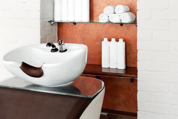 Cuenco de peluquería en el interior del salón de belleza. lavabo para lavar el cabello, procedimientos de spa para el cuidado del cabello