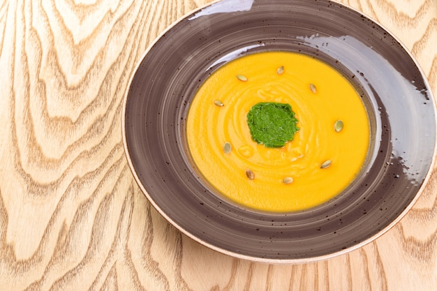 Cuenco de sopa de la calabaza en fondo de madera rústico.