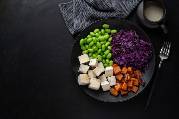 Cuenco vegano apetitoso sabroso con tofu en placa. vista superior