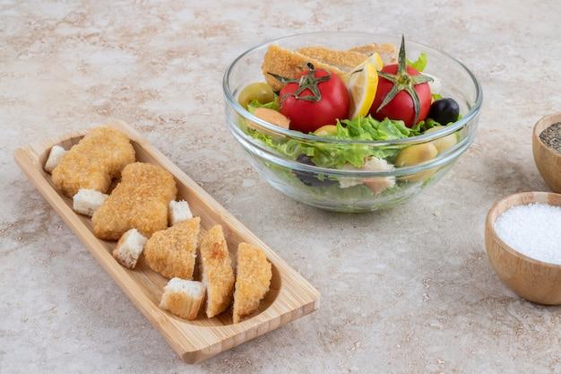 Cuenco de verduras, sal, pimienta negra y palitos de pescado picados en una bandeja pequeña