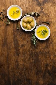 Cuencos de aceite de oliva con romero y vista superior del espacio de copia