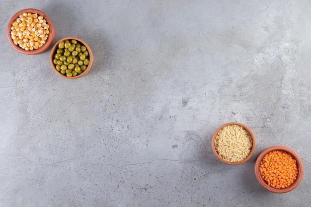 Cuencos de barro con arroz crudo, lentejas, guisantes y callos sobre mesa de piedra.
