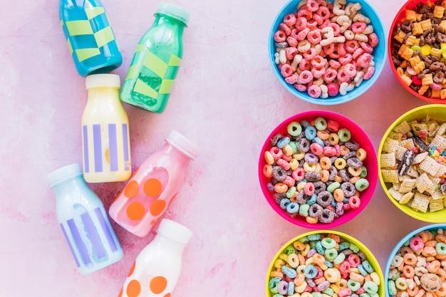 Cuencos brillantes de cereales con leche en mesa