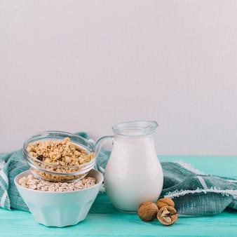 Cuencos de cereales; tarro de leche y nueces en mesa de madera