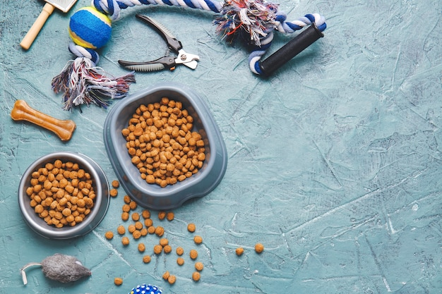 Cuencos con comida para mascotas y accesorios sobre fondo de color