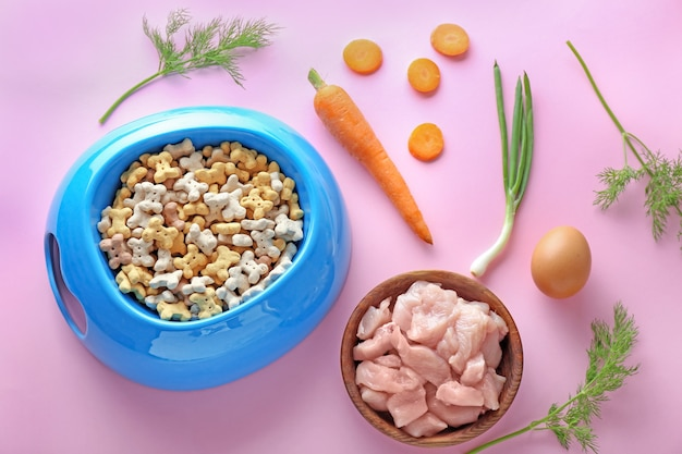 Cuencos con comida para mascotas y productos naturales sobre fondo de color