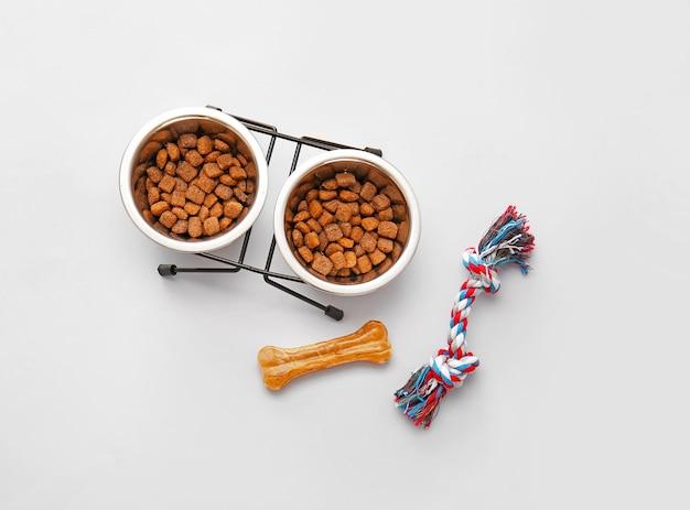 Cuencos con comida seca para mascotas, hueso masticable y cuerda de algodón para caza sobre fondo claro