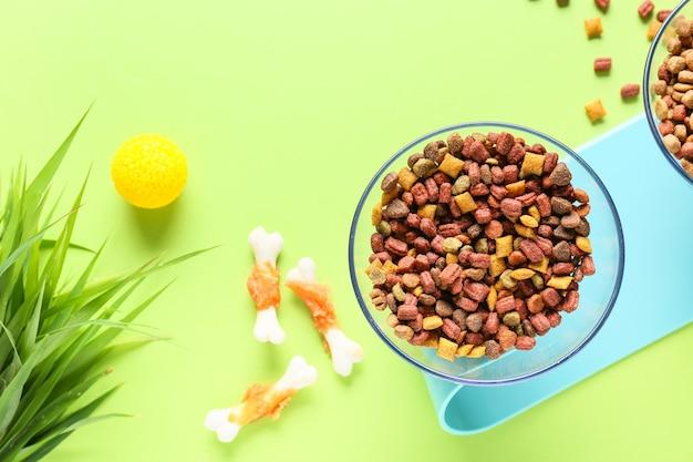 Cuencos con comida seca para mascotas y pasto en color