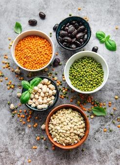 Cuencos con diferentes tipos de legumbres sobre un fondo de hormigón gris