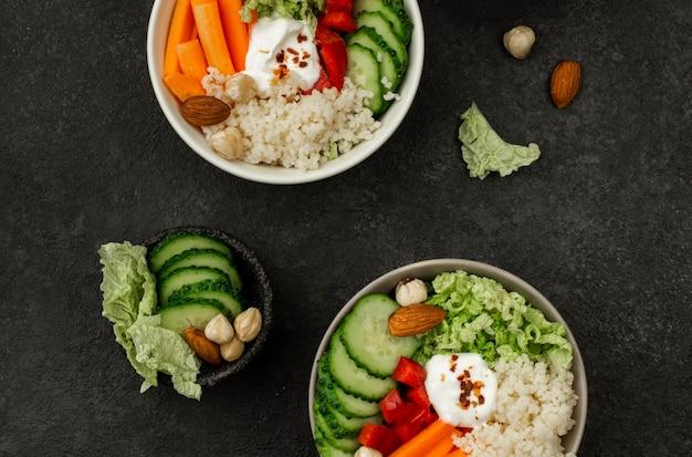 Cuencos de ensalada de verduras de vista superior con cuscús y pepinos