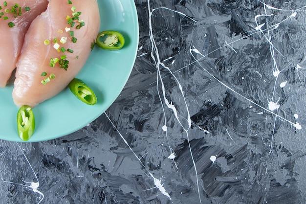 Cuencos de especias y pechuga de pollo en un plato, sobre el fondo de mármol.