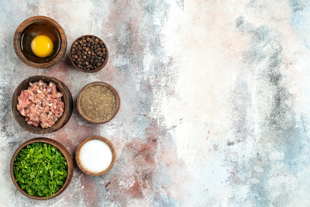 Cuencos de fila vertical de vista superior con verduras de carne yema de huevo pimienta en polvo sal de pimienta negra en el espacio libre de la superficie desnuda