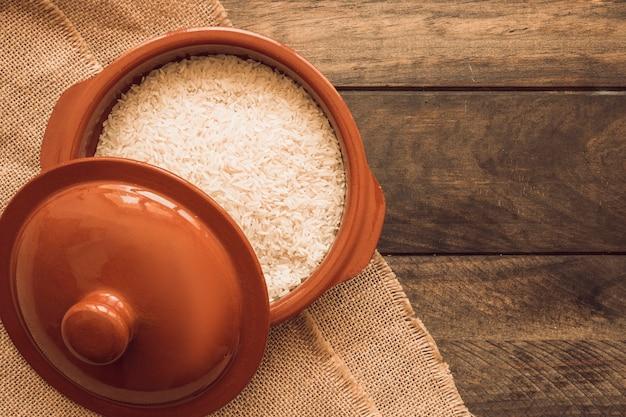 A los cuencos de granos de arroz abiertos con tapa en la mesa de madera