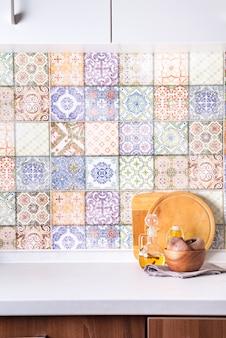 Cuencos de madera y aceite de oliva sobre una encimera de piedra en una pared de azulejos de colores antiguos, fachada interior de cocina