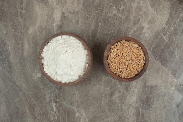 Cuencos de madera de harina y cebada sobre fondo de mármol. foto de alta calidad
