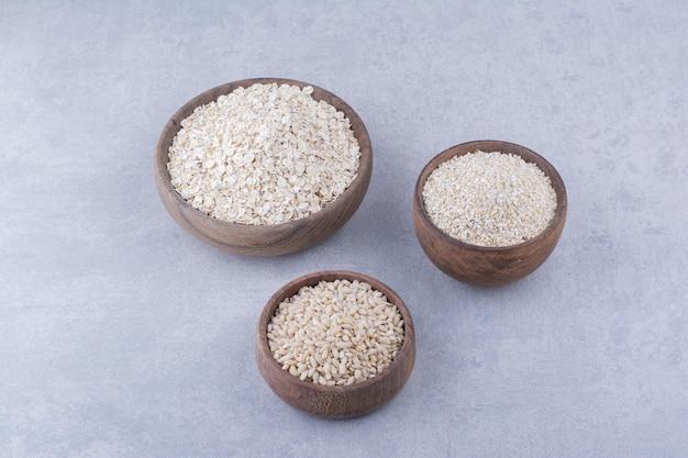 Cuencos de madera llenos de arroz, avena y copos de avena sobre superficie de mármol
