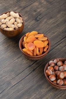 Cuencos de madera llenos de nueces saludables con frutos secos de albaricoque sobre mesa de madera.