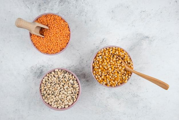 Cuencos de maíz crudo, frijoles y lentejas rojas sobre superficie de mármol.