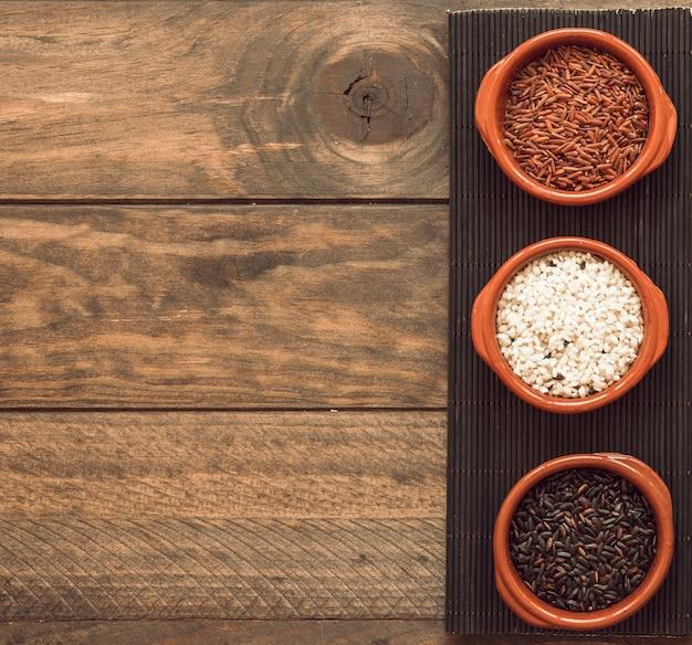 Cuencos orgánicos de los granos del arroz marrón y blanco en la bandeja sobre la tabla de madera