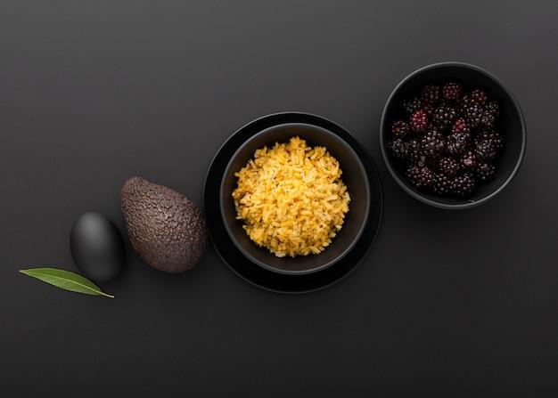 Cuencos oscuros con arroz y aguacate en la mesa oscura