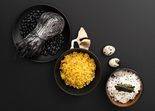 Cuencos oscuros con pasta y arroz sobre un fondo oscuro