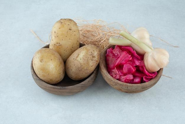 Cuencos de patatas hervidas y col lombarda en escabeche con ajo.