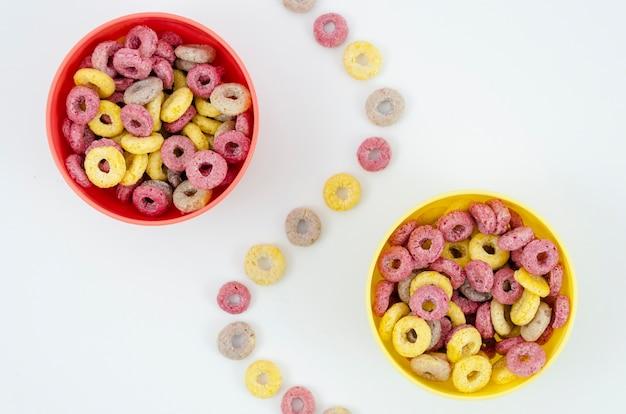 Cuencos rojos y amarillos separados por un rastro de aros de frutas