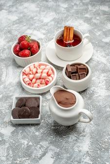 Cuencos de vista inferior con caramelos de cacao, fresas, chocolates, té con canela y semillas de anís en la mesa gris-blanca