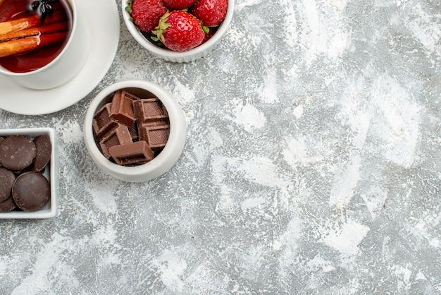 Cuencos de vista de la mitad superior con fresas y chocolates y té de semillas de anís y canela en la parte superior izquierda del suelo gris-blanco