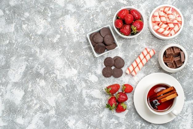 Cuencos de vista superior con fresas, chocolates, caramelos y té de semillas de anís y canela en el lado derecho del suelo blanco grisáceo