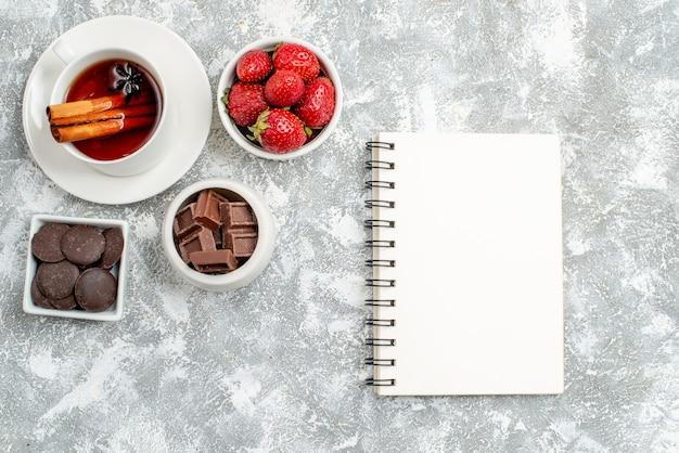 Cuencos de vista superior con fresas y chocolates, té de semillas de anís canela y un cuaderno sobre el suelo gris-blanco