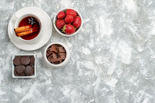 Cuencos de vista superior con fresas y chocolates y té de semillas de anís y canela en la parte superior izquierda del suelo gris-blanco