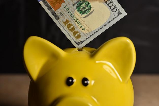 Cuenta de dinero en el cerdo de la hucha amarilla en
