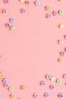 Cuentas del alfabeto sobre fondo rosa