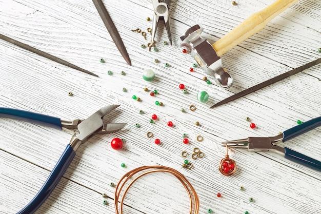 Cuentas de colores, alambre de cobre y herramientas de joyería en una mesa de luz. cable enrrollado